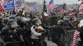 Cảnh sát chặn người biểu tình cố gắng vượt qua hàng rào an ninh để xâm nhập tòa nhà Quốc hội Mỹ ở Washington, DC ngày 6/1/2021. Ảnh: AFP/TTXVN