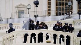 Cảnh sát theo dõi những người biểu tình cố gắng vượt qua hàng rào cảnh sát ngày 6-1 tại Điện Capitol ở Washington. Ảnh: Julio Cortez, AP