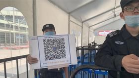 Nhân viên bảo vệ cầm tấm biển có mã QR để du khách quét và tải xuống ứng dụng tại lối vào của Trung tâm Triển lãm và Hội nghị Thâm Quyến vào 12-4-2021. Ảnh: Yujie Xue/SCMP