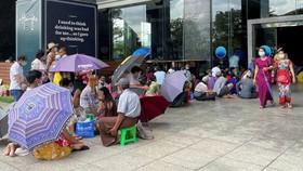 Người dân Yangon mang theo ghế đẩu và ô để khiến việc chờ đợi lâu bên ngoài các ngân hàng dễ chịu hơn. © Reuters