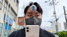 Paeng Min-wook trình diễn việc sử dụng Con Mắt Thứ Ba khi vừa lướt điện thoại vừa đi bộ trên đường phố Seoul. Nguồn: NYP.