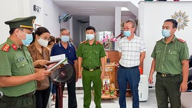 Lee Kwan Young (2nd, R), deputy head of South Korean Association in central Vietnam, is arrested at his residence in Da Nang for bringing in fake foreign experts, July 9, 2021. Photo by VnExpress/Bao Nam.