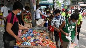 Người dân thu thập các gói thực phẩm miễn phí từ một ngân hàng thực phẩm cộng đồng ở thành phố Quezon, Manila, vào ngày 21 tháng 4 năm 2021. ẢNH: AFP