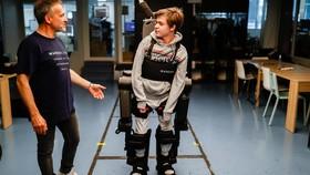 Jean-Louis Constanz hướng dẫn cậu con trai Oscar 16 tuổi của mình sử dụng bộ khung xương trợ lực tại trụ sở Wandercraft, Paris, Pháp. Nguồn ảnh: Reuters.