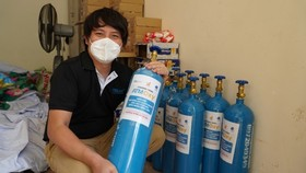 Businessman Hoang Tuan Anh holds an oxygen tank as part of the Oxy ATM initiative in Ho Chi Minh City. Photo courtesy of Hoang Tuan Anh.