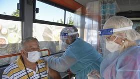 Một người đàn ông được tiêm vaccine Johnson & Johnson trên chiếc xe buýt tiêm chủng ở Bucharest, Romania. Ảnh: APNews.