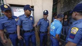 Cảnh sát Philippines và một sĩ quan cộng đồng địa phương trong chiến dịch chống ma túy bất hợp pháp ở thành phố Quezon, phía đông Manila, năm 2018. Ảnh: EPA-EFE