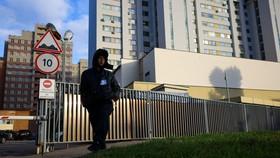 Một nhân viên bảo vệ tuần tra bên ngoài một tòa nhà đặt văn phòng thông tin NATO hôm 18/10/2021 ở Moscow. Dimitar Dilkoff/Agence France-Presse — Getty Images