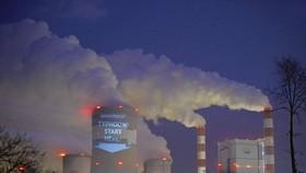 Một khẩu hiệu được các nhà hoạt động chiếu sáng lên tháp làm mát của Nhà máy điện Belchatow, nhà máy nhiệt điện than lớn nhất châu Âu, ở Ba Lan vào tháng 11/2013. (Nguồn: Reuters).