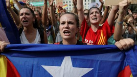 Một phụ nữ cầm cờ ly khai của Catalonia trên đường phố Barcelona hôm 2/10. Ảnh: Reuters.