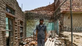 Một người đàn ông Ấn Độ đứng trên đống đổ nát của ngôi nhà đã bị phá hủy trong cơn bão. (Nguồn: Sky News)