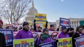 Các nhân viên liên bang cầm khẩu hiệu đòi mở cửa chính phủ.    Ảnh:AP.
