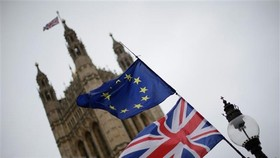 Cờ Anh (phía dưới) và cờ EU (phía trên) bên ngoài tòa nhà Quốc hội Anh ở thủ đô London. (Nguồn: THX/ TTXVN)g trường hợp 2 bên không đạt được thỏa thuận.