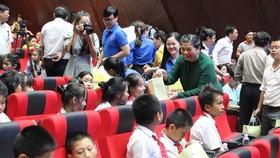 Phó Chủ tịch Quốc hội Tòng Thị Phóng xuống từng hàng ghế để tặng quà cho các em thiếu nhi. Ảnh: congthuong.vn