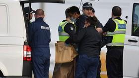 Cảnh sát cầm túi chứa các bằng chứng của vụ tấn công. Ảnh: Reuters