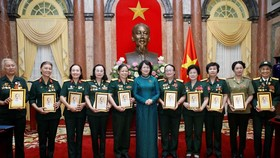 Phó Chủ tịch nước Đặng Thị Ngọc Thịnh tặng chân dung Chủ tịch Hồ Chí Minh cho các đại biểu nữ bộ đội Trường Sơn, thanh niên xung phong, dân quân hỏa tuyến, công nhân giao thông thời kỳ kháng chiến. Ảnh: TTXVN
