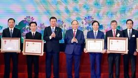 Thủ tướng Nguyễn Xuân Phúc trao tặng Huân chương Độc lập hạng Ba và Huân chương Lao động hạng Nhất cho các tập thể.  Ảnh: TTXVN