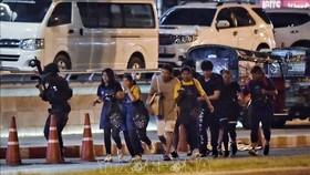 Các con tin được lực lượng an ninh Thái Lan hỗ trợ rời khỏi trung tâm thương mại Terminal 21, nơi nghi phạm Jakrapanth Thomma vụ xả súng và bắt giữ con tin. Ảnh: AFP/TTXVN
