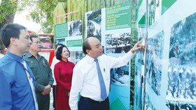Thủ tướng Nguyễn Xuân Phúc thăm không gian trưng bày hình ảnh về lực lượng thanh niên xung phong. Ảnh: VIẾT CHUNG
