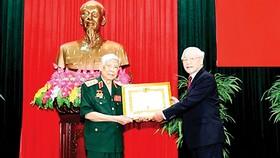 Tổng Bí thư, Chủ tịch nước Nguyễn Phú Trọng, Bí thư Quân ủy Trung ương, trao Huy hiệu 70 năm tuổi Đảng tặng đồng chí Lê Khả Phiêu ngày 25-8-2019. Ảnh: TTXVN