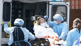 Nhân viên y tế chuẩn bị chuyển bệnh nhân mắc Covid-19 tới bệnh viện ở Brooklyn, New York (Mỹ). Ảnh: AFP/TTXVN