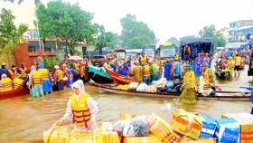 Người dân đổ về rốn lũ huyện Lệ Thủy, tỉnh Quảng Bình, để cứu trợ đồng bào bị ngập lụt. Ảnh: NGỌC OAI