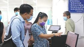 Tìm hiểu dịch vụ công trực tuyến tại UBND huyện Hóc Môn. Ảnh: MẠNH HÒA
