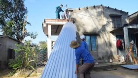 Các bạn trẻ hỗ trợ người dân lợp lại nhà sau bão số 9