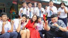 Cô Lê Thị Kim Chi, Giám đốc Trung tâm Hỗ trợ phát triển giáo dục hòa nhập Tân Bình (quận Tân Bình) cùng các học trò của mình. Ảnh: HOÀNG HÙNG