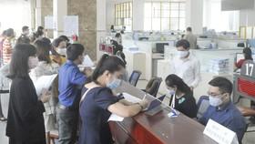 Làm hồ sơ thuế tại Cục Thuế TPHCM. Ảnh: CAO THĂNG