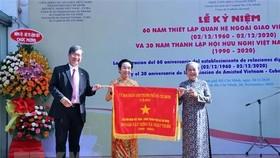 Ông Vương Đức Hoàng Quân, Chủ tịch Liên hiệp các tổ chức hữu nghị TPHCM, trao Cờ truyền thống của UBND TP tặng Hội hữu nghị Việt Nam-Cuba TPHCM. Ảnh: TTXVN