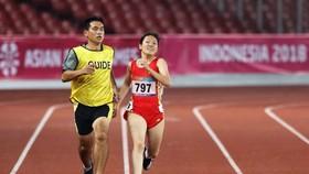 HLV Nguyễn Văn Phương (trái) dẫn VĐV điền kinh khuyết tật Việt Nam thi đấu ở Asian Paragames 2018. Ảnh: P.NGUYỄN