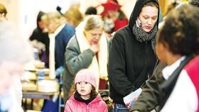 Người Mỹ xếp hàng chờ nhận thực phẩm cứu trợ ở Michigan. Ảnh: AP