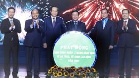 Chủ tịch nước Nguyễn Xuân Phúc và các đại biểu chứng kiến Lễ phát động Tháng công nhân và Tháng hành động về an toàn, vệ sinh lao động năm 2021. Ảnh: TTXVN