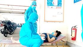 2 bác sĩ khám thai một cư dân trong khu vực phong tỏa. Ảnh: KHÁNH HƯNG