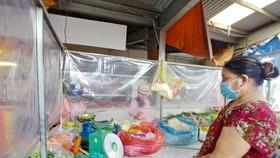 Tiểu thương bán hàng ở chợ truyền thống làm vách ngăn bảo đảm điều kiện an toàn phòng chống dịch. Ảnh: hcmcpv
