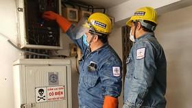 Nhân viên ngành điện thành phố kiểm tra hệ thống điện cho khách hàng