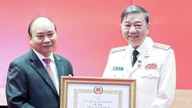 Chủ tịch nước Nguyễn Xuân Phúc trao tặng Huy hiệu 40 năm tuổi Đảng cho Đại tướng Tô Lâm, Bộ trưởng Bộ Công an. Ảnh: TTXVN