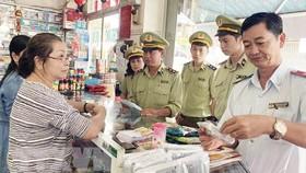 Lực lượng Quản lý thị trường kiểm tra, nhắc nhở các hiệu thuốc tân dược không tăng giá bán khẩu trang y tế. Ảnh: TTXVN