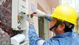 Công nhân điện lực đang thay điện kế điện tử cho khách hàng