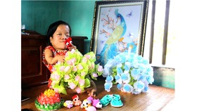 Chị Nguyễn Thị Hòa cùng những bình hoa, bức tranh xinh xắn do chị làm, được cộng đồng mạng chia sẻ