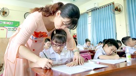 Cô Phạm Thị Thùy Minh, giáo viên chủ nhiệm lớp 1/7, Trường Tiểu học Núi Thành (quận Hải Châu, TP Đà Nẵng) hướng dẫn các em tập viết. Ảnh: XUÂN QUỲNH