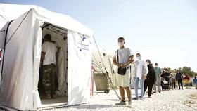 Người di cư xếp hàng chờ xét nghiệm virus SARS-CoV-2 ở trại tị nạn Moria trên đảo Lesbos, Hy Lạp. Ảnh: AP