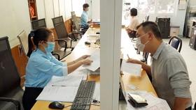 Người dân làm thủ tục hành chính tại phường 6 (quận 3) - phường sẽ được sáp nhập với phường 7, 8 để thành phường Võ Thị Sáu. Ảnh: HOÀNG HÙNG
