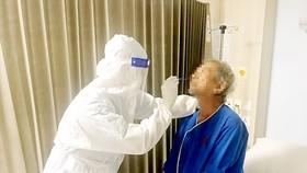 Nhân viên Bệnh viện Gia An 115 lẫy mẫu xét nghiệm sàng lọc SARS-CoV-2 cho người bệnh vào đêm 12-5