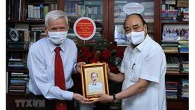 Chủ tịch nước Nguyễn Xuân Phúc thăm nhà báo Đặng Minh Phương. Ảnh: TTXVN