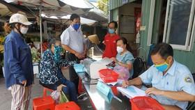 Người đi chợ Bình Thới khai báo y tế trước khi nhận phiếu đi chợ theo thứ tự