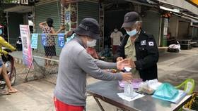 Người dân khai báo y tế, đo thân nhiệt, sát khuẩn khi vào mua sắm tại chợ An Hội (quận gò Vấp) sáng 9-7. Ảnh: BÙI ANH TUẤN