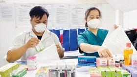 Nhân viên Trạm Y tế phường Nguyễn Cư Trinh, quận 1, TPHCM đang phân thuốc cung cấp bệnh nhân F0 tại địa phương. Ảnh: HOÀNG HÙNG