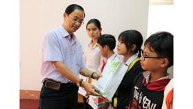 Nhà báo Trần Văn Phong, Trưởng Văn phòng đại diện Báo Sài Gòn Giải Phóng tại khu vực Đông Nam bộ, trao học bổng cho học sinh nghèo huyện Lộc Ninh